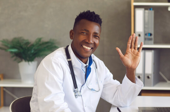 Headshot of happy young African-American doctor saying hello to patients. Portrait of handsome black man in white lab coat looking at camera, smiling and waving hand