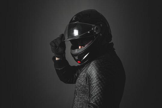 Motorbiker is turning around and open a helmet visor on a dark background.