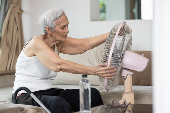 Overheated asian senior woman sweating,high temperature in sunny day while stay at home,cooling herself in front of an electric fan,old elderly suffering from heat,hot summer weather,lifestyle concept