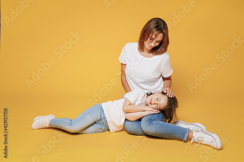 Full body length happy woman in basic white t-shirt sit on floor child baby girl 5-6 years old sleep. Mom mum little kid daughter isolated on yellow color background studio. Mother's Day love family.