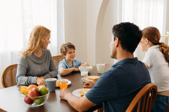 Cheerful caucasian family enjoying meal together while having breakfast sitting at the table at home and listening to young boy