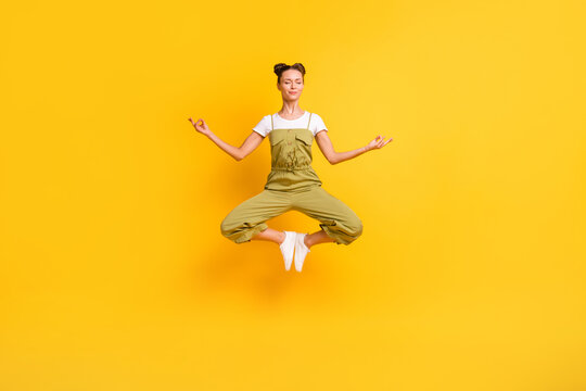 Full length body size view of pretty calm dreamy girl jumping meditating sit lotus pose isolated over bright yellow color background
