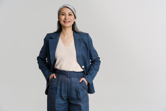 Asian mature woman smiling while holding hands in her pockets