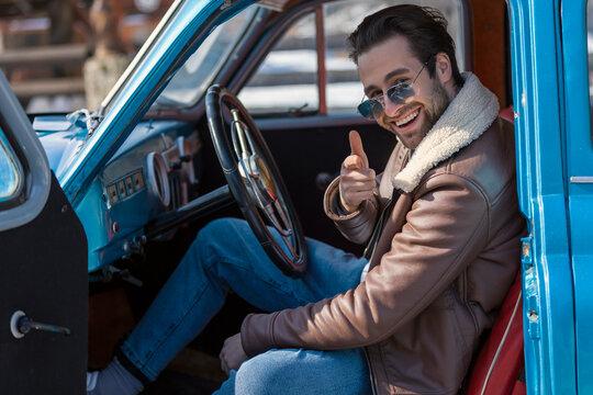 a man sitting in a retro car