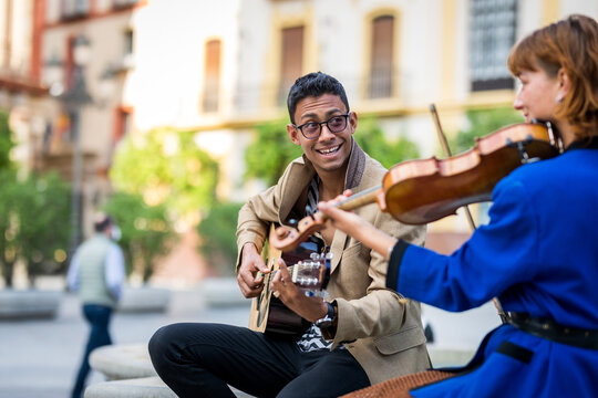 Musicians couple playing and having fun on the street. Latin guitarist and Caucasian violinist.