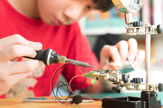 STEM education and 21st century skills concept. Young Asian teenager, kid is soldering water moisture sensor circuit board with grip hand desktop stand. DIY school science and technology project.