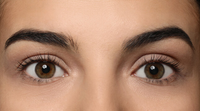 Young woman after eyelash lamination, closeup. Professional service