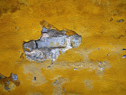 Empty textured yellow plaster wall with old bricks behind