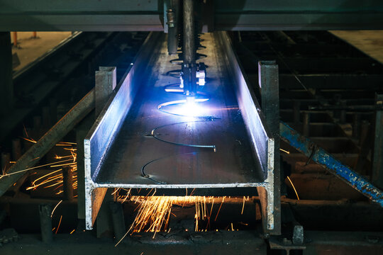 Drilling steel structure with sparks fly from drill machine in cellular beam fabrication process for construction.