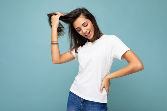 Portrait of young beautiful happy smiling brunette woman wearing trendy white t-shirt with empty space for mock up. Sexy carefree female person posing isolated near blue wall in studio with free space