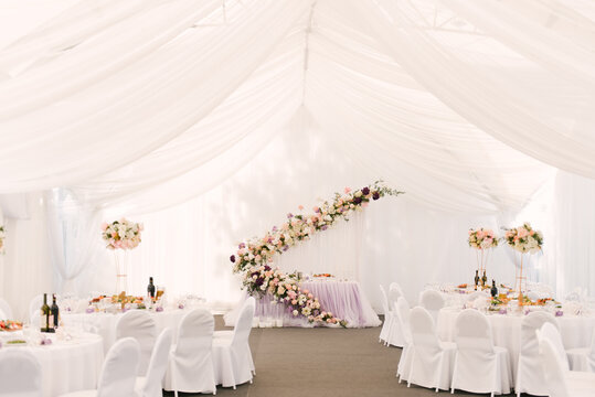 Luxury wedding dinner in a large beautiful tent, beautiful decor for the wedding of the white hall decorated with flowers