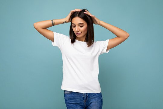 Photo of positive happy sexy young beautiful brunette woman with sincere emotions wearing stylish white t-shirt for mockup isolated over blue background with empty space