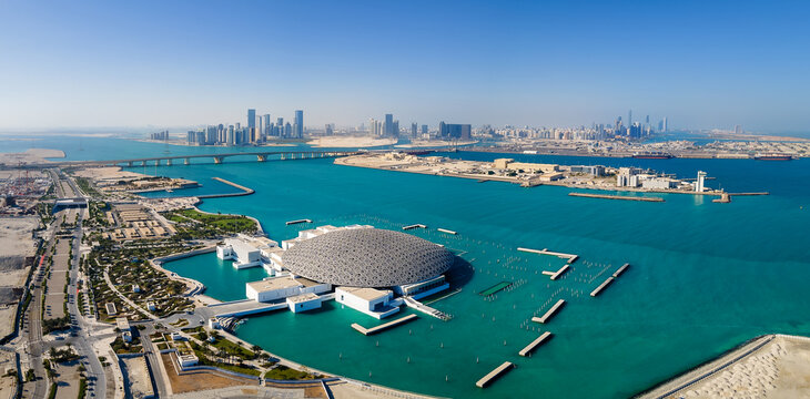 Abu Dhabi, United Arab Emirates - April 6, 2021: Louvre museum and Abu Dhabi aerial emirate skyline in the UAE capital