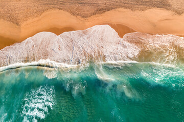 Aerial view of Atlantic ocean sandy beach with breaking waves. Top view of sea coast with turquoise water