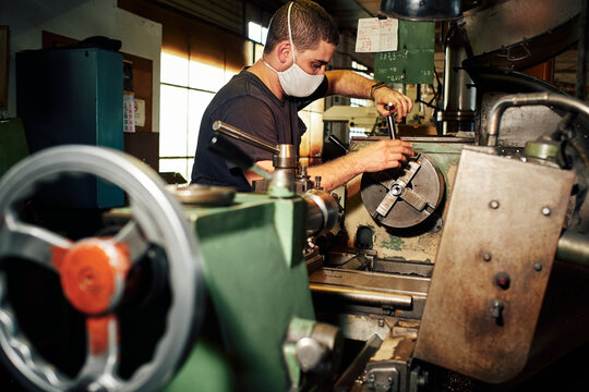 Closeup shot of a Hispanic mechanical engineer controlling the lathe machine in a factory