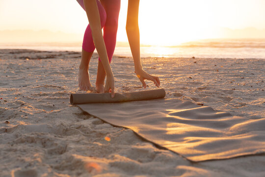 Mid section of caucasian woman rolling yoga mat at the beach