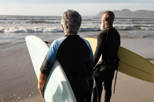Diverse senior couple on beach holding surfboards looking out to sea