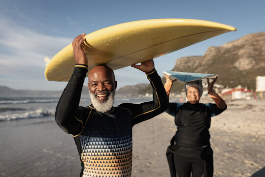 Portrait of senior african american couple carrying surf board on their head on the beach