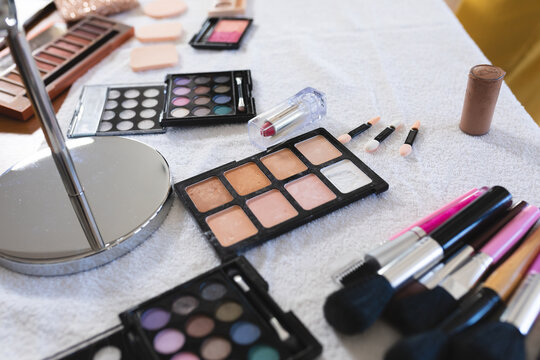 Selection of makeup brushes, sponges, eye shadows, lipstick,face powders and a mirror on a table top
