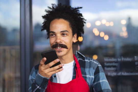 Happy mixed race male barista with moustache leaning in the doorway of cafe talking on smartphone