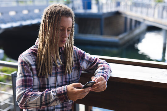 Mixed race man with dreadlocks standing outside cafe using smartphone