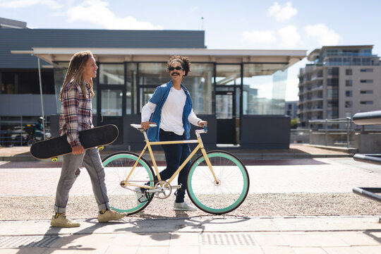 Two happy mixed race male friends wheeling bicycle carrying skateboard in the street and talking