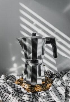Bodegón de cafetera italiana plateada y mango negro, sobre paños de cocina de cuadros y un tapete de esparto. De fondo luces y sombras que dejan los primeros rayos de sol que entran por la ventana
