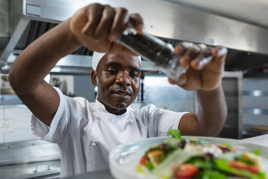 Happy african american professional chef finishing dish before serving