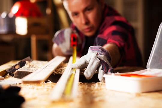 Young male carpenter working in workshop. Woodworker measuring wooden plank..