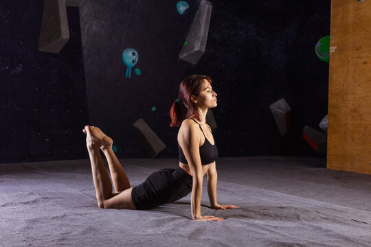 Athletic young woman practicing yoga in indoor climbing gym