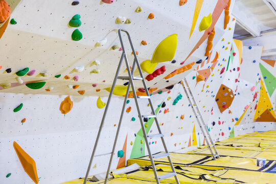 Empty indoor bouldering gym with ladders next to climbing walls