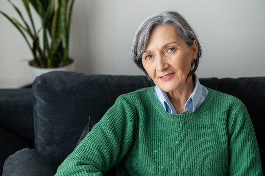 A portrait of a charming beaming old lady posing and looking at the camera, gray-haired senior mature woman sitting in the living room, wearing a casual green jumper, resting and smiling