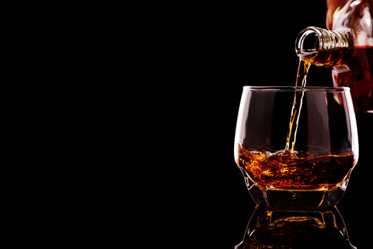 whiskey pouring in glasses with ice cubes isolated on black background. have space for text