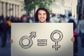 Fototapeta Gender equality concept as young man holding a big banner with male and female symbol, as protest demonstration message on a crowded city street. Sex rights and discrimination as a major social issue