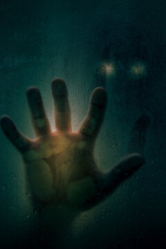 Horror scene of a man with hand against wet shower glass and dark cityscape background. Toned image. Horror concept