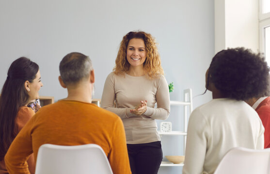 Happy beautiful woman making presentation standing in front of diverse audience. Psychologist or coach talking to group of young and mature people. Team of company workers listening to female speaker