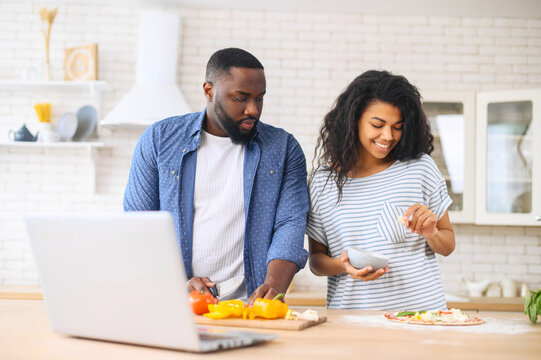 Excited young African American couple following steps from watching online cooking classes, learning how to make pizza, watching video blog course from laptop in the kitchen, placing vegetables