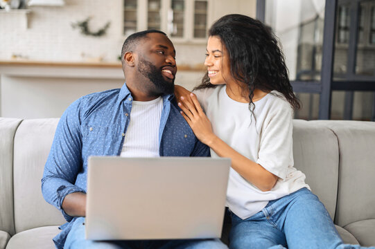 Cute African-American couple in love spends leisure together with the laptop at home, boyfriend and girlfriend sitting on the couch in embraces and looks at each other tenderly