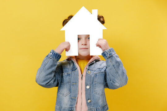 Pretty little girl holding paper house, homeless housing and home protection insurance concept, international day of families, foster home care, family day care, isolated over yellow studio background