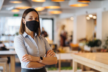 Fototapeta Woman business owner wearing face mask after reopening restaurant, arms folded obraz
