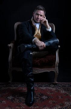 A handsome Regency gentleman sitting in a red velvet chair in a darkened room