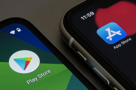 Portland, OR, USA - Apr 21, 2021: Google Play Store and Apple App Store icons are seen respectively on a Google Pixel smartphone and an iPhone.