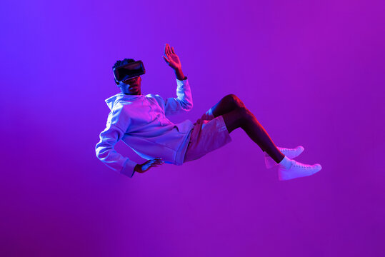 Amazed young African man wearing VR glass headset levitating in the air on futuristic purple cyberpunk neon light background