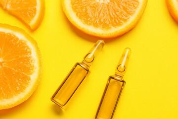 Fototapeta Ampules with vitamin C injection and orange fruit slices on color background obraz