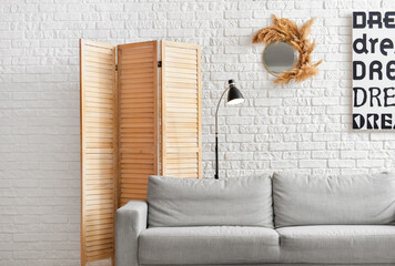 Comfortable sofa and folding screen near brick wall