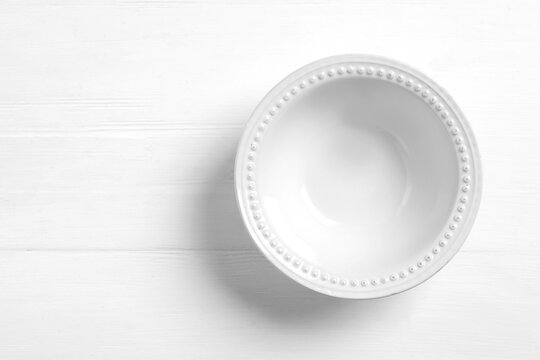 Empty ceramic bowl on white wooden table, top view. Space for text