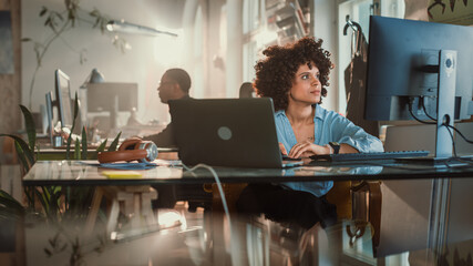 Creative Office: Young Black Woman Sitting at Her Desk Working on Computer. Charmingly Authentic Software Developer, Social Media Marketing Specialist Creating Content, Using Devices. Wide Shot
