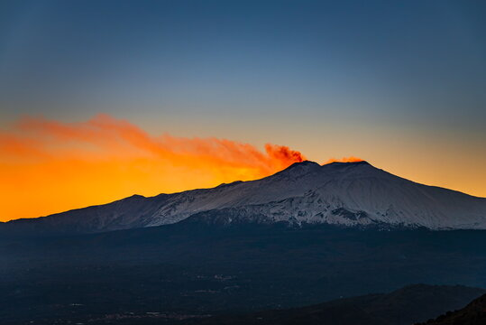 Silhouette of Mount Etna smoking in red during sunset