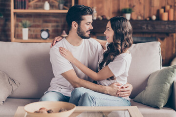 Fototapeta Portrait of attractive cheerful couple life partners embracing spending day weekend sitting on divan at home house indoor