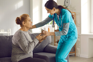 Treatment, care and support. Friendly young doctor visiting female patient at home. Caring nurse at clinic or assisted living facility helping senior woman take medicine and giving her glass of water
